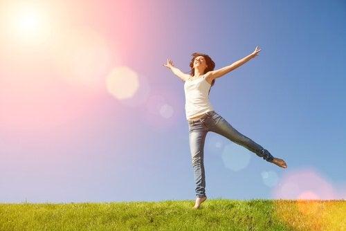 Glad kvinde hopper på eng
