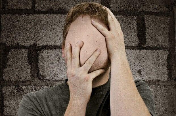 Mand uden ansigt rører ved sig selv og illustrerer agnosi
