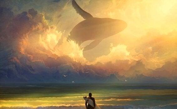 hval i himlen foran surfer på strand