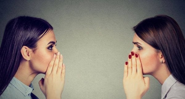To kvinder, der kan lide at sladre, hvisker til hinanden
