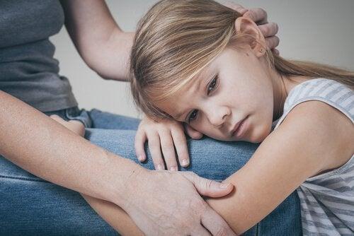 Trist pige lægger hoved på voksens knæ og har problemer med kommunikation mellem forældre og børn