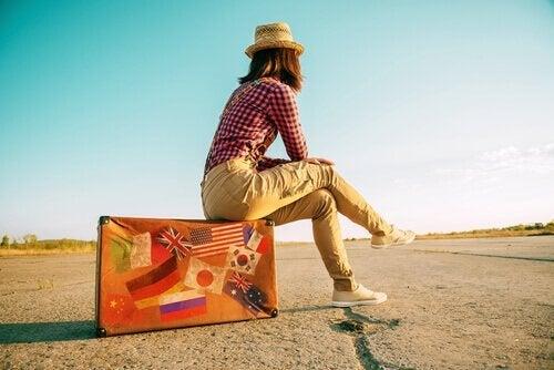 kvinde sidder på kuffert og er besat af at rejse