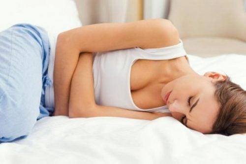Kvinde med PMS ligger på seng
