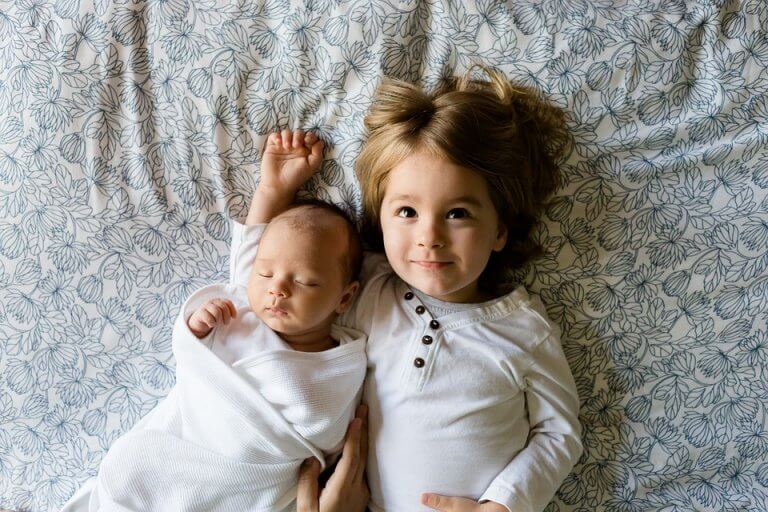 To søskende ligger i en seng