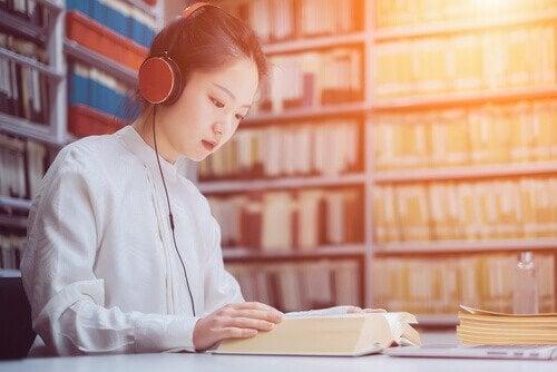 Kvinde lytter til musik, mens hun læser