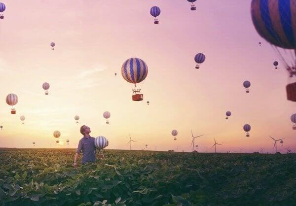 Mand fanger luftballoner på mark i sin søgen efter lykke gennem eudaimonia