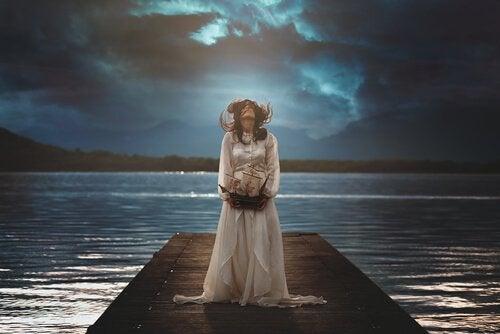 Kvinde står på bro ved sø om natten