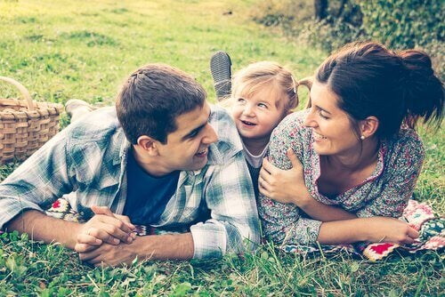 Par med datter ligger på græs