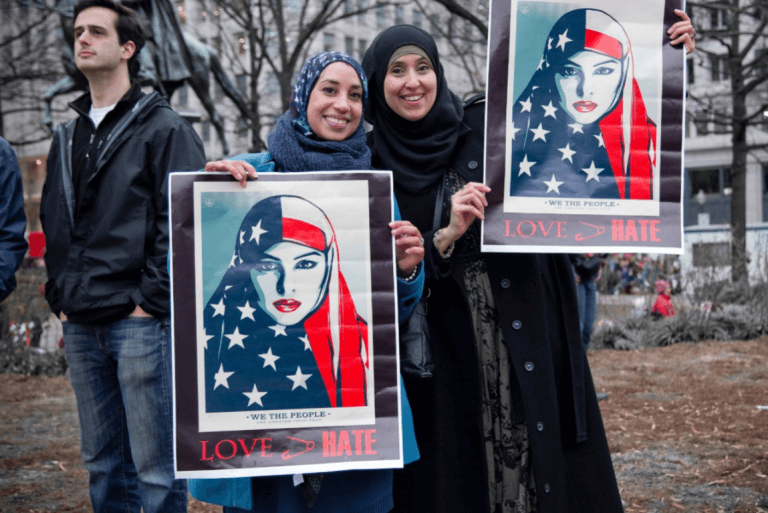 Kvinder holder plakat op i kamp mod xenofobi