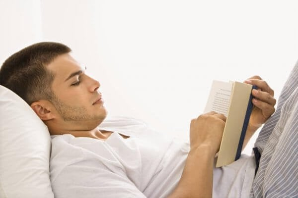 Mand med bog i seng nyder at læse før sengetid