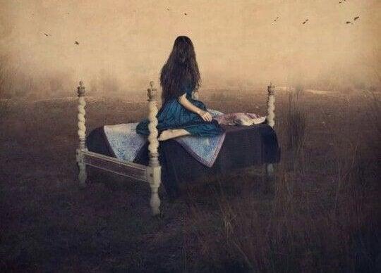 Kvinde sidder i seng