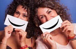 To kvinder holder tegnede smil op foran munden