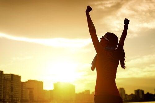 Person med hænderne over hovedet foran solopgang