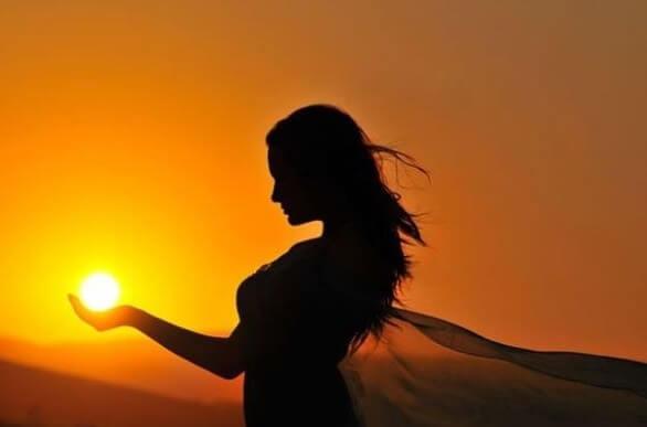 Kvinde med sol i hånd ønsker at genvinde positiv energi