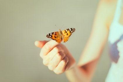 Kvinde med sommerfugl på finger