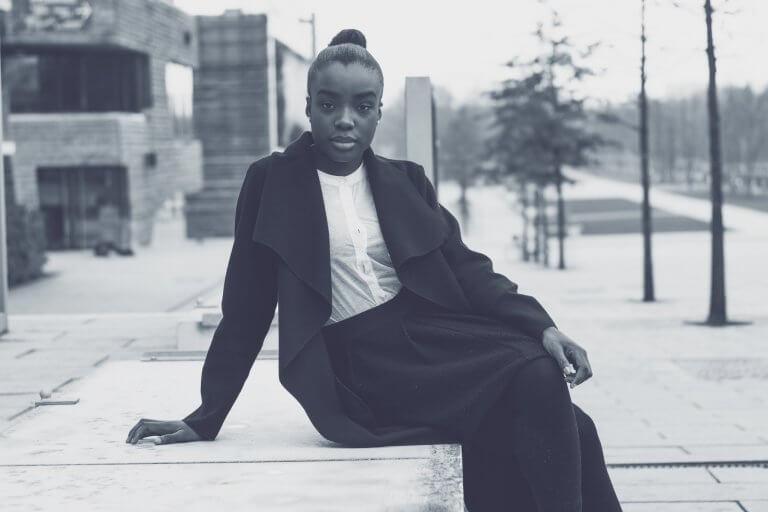 Kvinde i sort foran bygninger