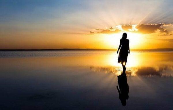 Kvinde går mod sol på strand for at genvinde positiv energi