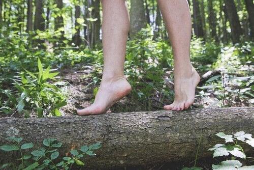 Kvinde går barfodet på træstamme og nyder en af de usædvanlige vaner med at gå i naturen