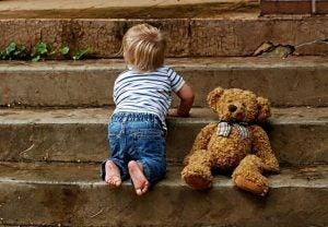 Barn på trappetrin med bamse viser babys udvikling