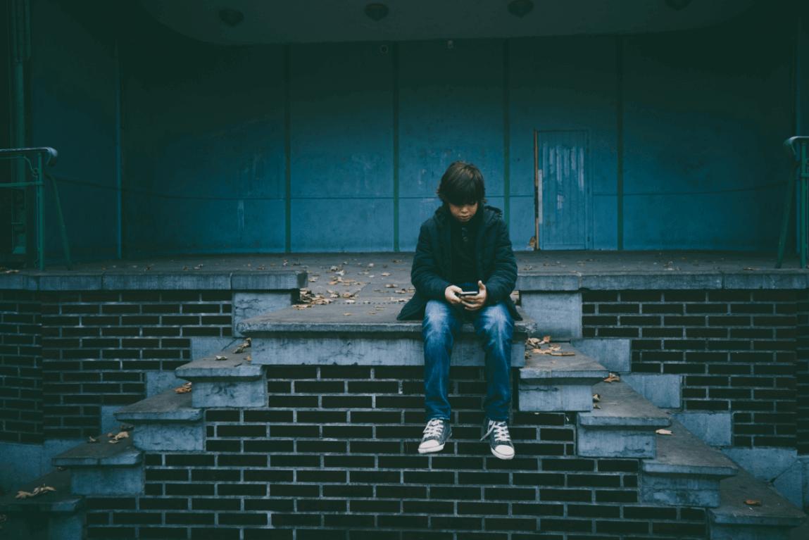 Trist dreng sidder alene på trappe for at illustrere, at det kan være svært at fortælle børn om dødsfald