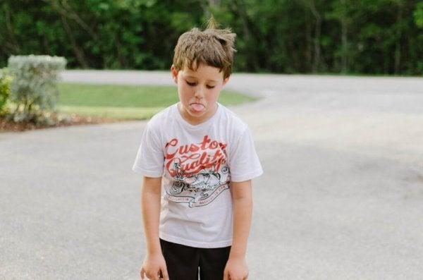 Dreng med raserianfald rækker tunge