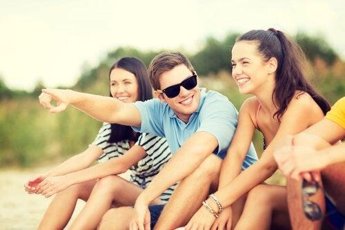 Venner griner sammen på strand