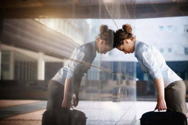 stresset kvinde sætter hoved mod væg