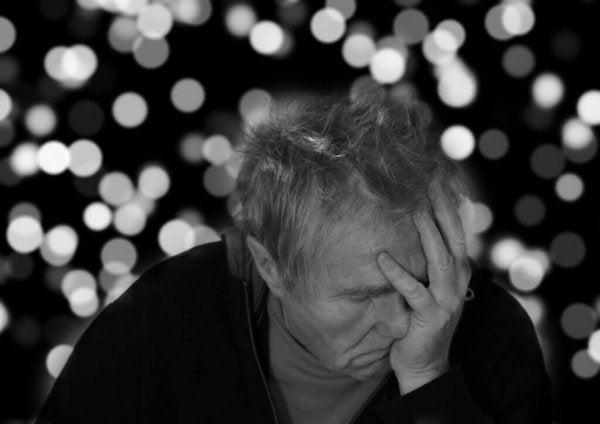 symptomerne på depression hos en ældre mand der holder sit hoved