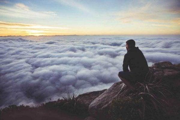 Mand sidder på toppen af bjerg og kigger ud på skyer
