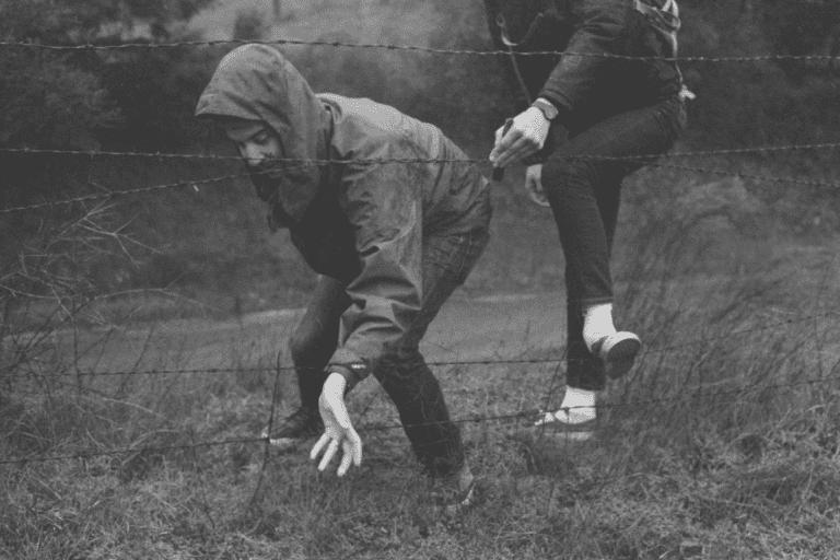 To personer kravler gennem hegn, da udfordringer kan maksimere din modstandsdygtighed