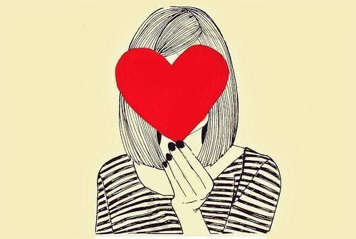 Kvinde holder et hjerte foran sit ansigt. Forelsket i dig selv.