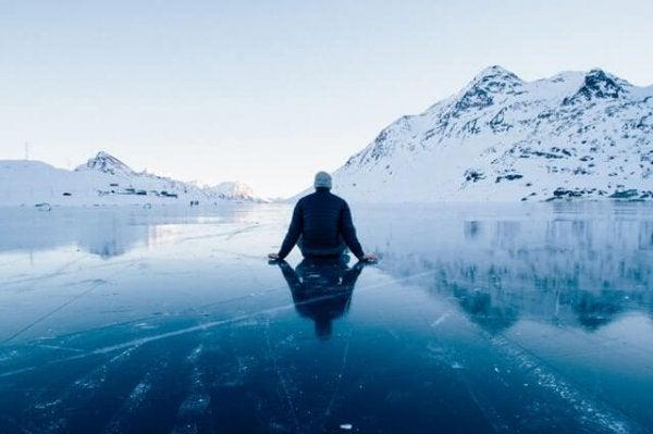 En mand sidder på is i bjergene og viser taknemmelighed
