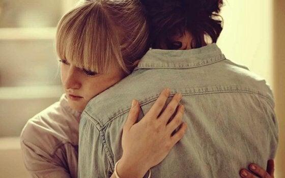 Kvinde krammer mand for at hjælpe ham med at komme igennem et tab