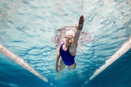 Kvinde svømmer i poolen i nyder fordele ved svømning