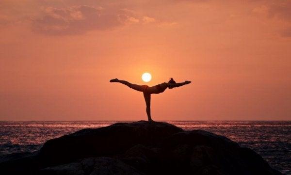 kvinde dyrker yoga ved solopgang. Motion er vigtigt