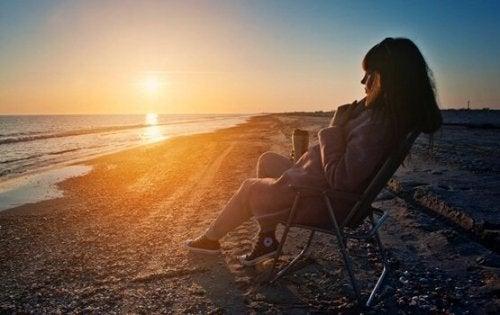 Kvinde sidder og kigger på solnedgang for at få et nyt perspektiv