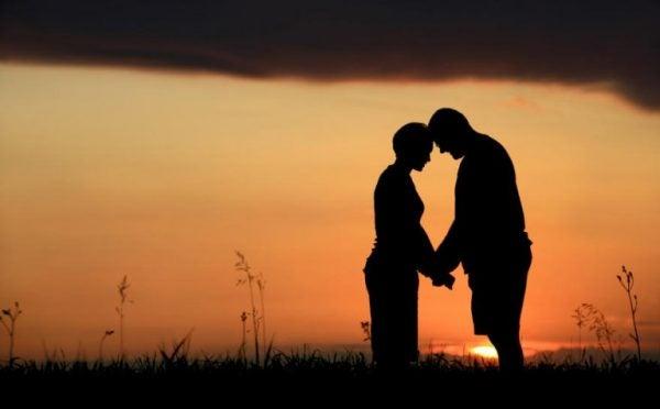 Par krammer foran solnedgang