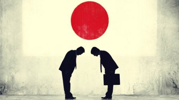 to mænd bukker med det japanske flag i baggrundet. japansk psykologi