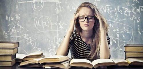 Kvinde sidder foran mange bøger og tager sig til hoved