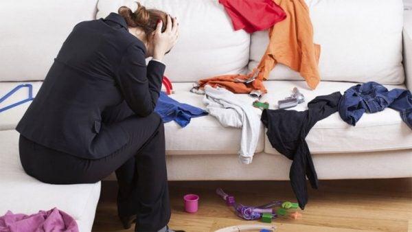tøj på sofa og frustreret kvinde over hendes uorden.