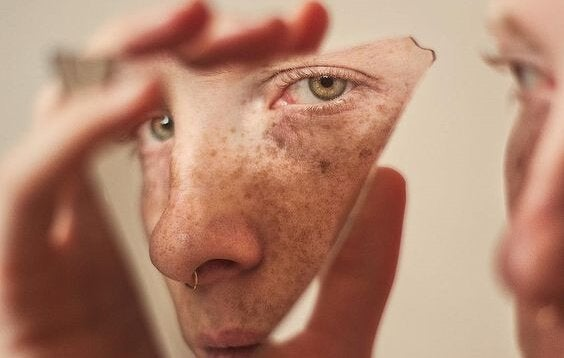 En kvinde kigger på sig selv i et ødelagt spejl. din egen allierede