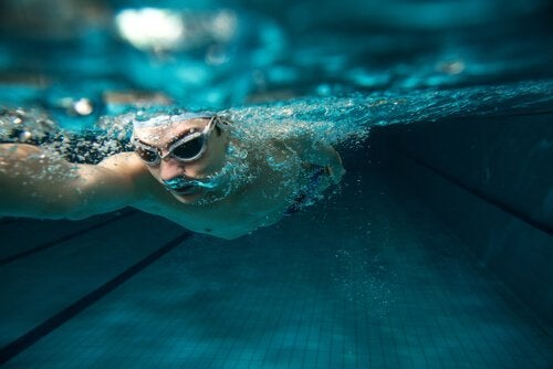 Mand svømmer under vandet og nyder fordele ved svømning