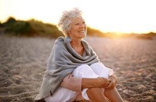 Ældre kvine sidder på stranden og dyrker sund aldring