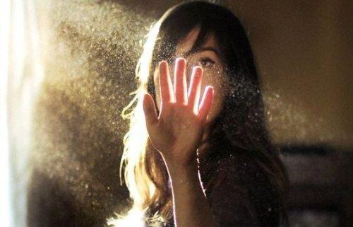 Kvinde sætter sin hånd op mod en lysstråle