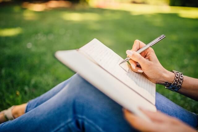 Kvinde skriver i sin journal og bruger terapeutiske skriveøvelser