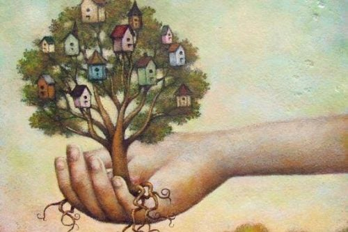 Holder et træ i hånden med rødder