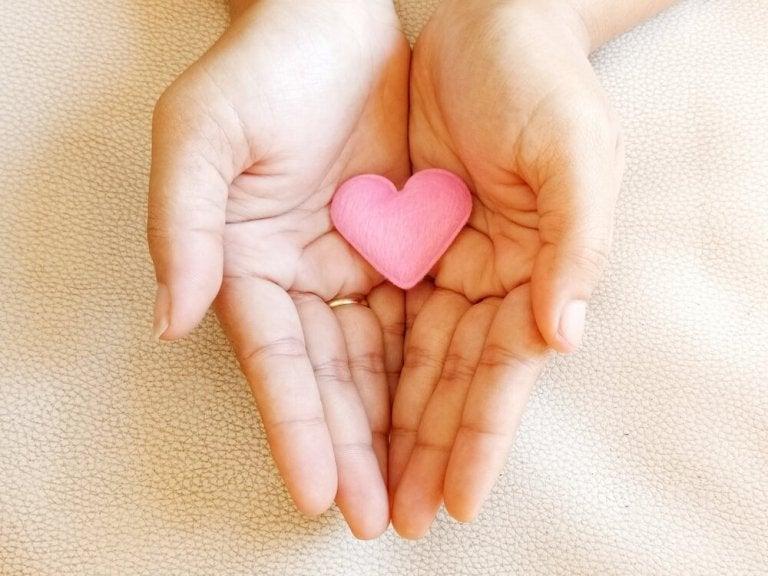 Hænder holder om hjerte og viser, at kærlighed sletter ikke fortiden