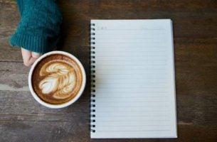 Journal ligger på et bord ved siden af en kop kaffe, hvor kvinde vil udføre terapeutiske skriveøvelser