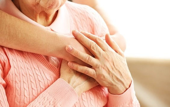 En kvinde krammer en ældre dame