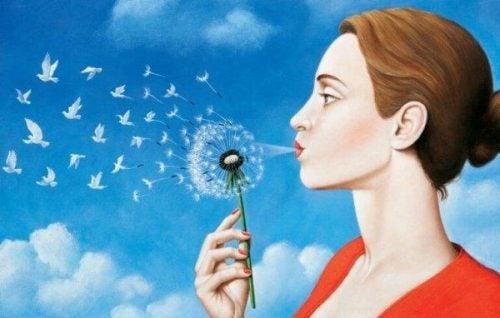Kvinde blæser mælkebøtte frø ud i det blå